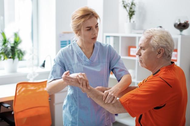 W pracy. przyjemna pielęgniarka patrząca na swojego pacjenta podczas masowania jego dłoni