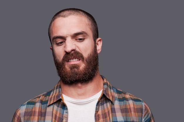 W przyjaźni z ironią. przystojny młody brodaty mężczyzna trzymający skrzyżowane ręce i wyrażający ironiczny uśmiech stojąc na szarym tle
