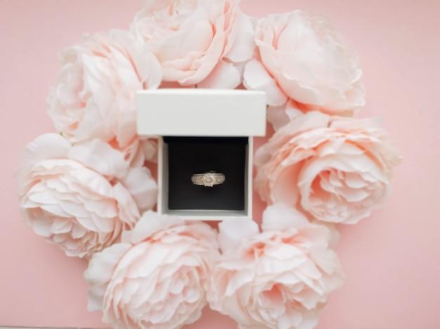 W pudełku na biżuterię znajduje się pierścionek w oprawie z różowych delikatnych piwonii na pięknym różowym tle. romantyczna koncepcja. płaski styl.