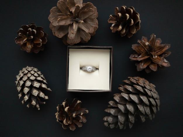 W pudełku na biżuterię znajduje się pierścionek z oprawą z pięknych brązowych szyszek na pięknym czarnym tle. romantyczna koncepcja. płaski styl.
