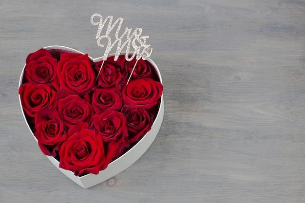 W pudełku w kształcie serca są pąki czerwonych róż, a wystrój liter to pan i pani