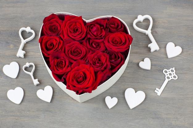 W pudełku w kształcie serca są pąki czerwonych róż, wokół drewnianych serc i kluczy