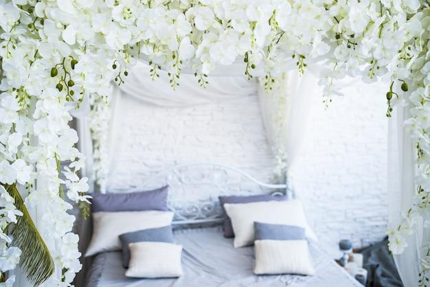 W pustej sypialni stoi piękne duże podwójne łóżko z białej tkaniny ozdobione girlandami z kwiatów