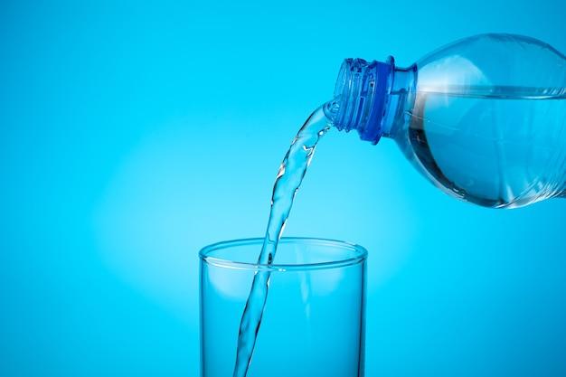 W pustej szklance wlej świeżą wodę na niebieskim tle.