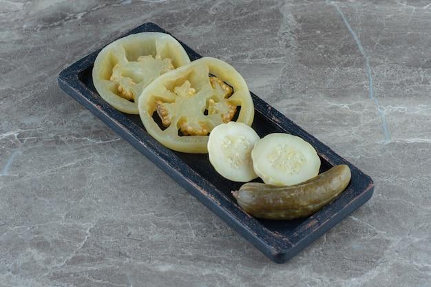 W puszkach zielony pomidor i ogórek na drewnianym talerzu.