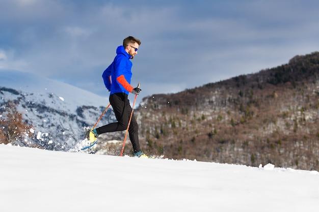 W rakietach śnieżnych z górki chłopiec biegnie z kijami