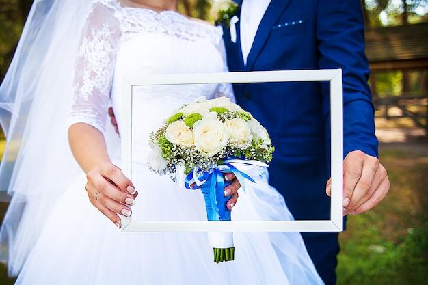 W rękach nowożeńców rama z bukietem ślubnym