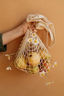 W rękach torebki ze świeżym plonem gruszek na prostym żółtym tle.