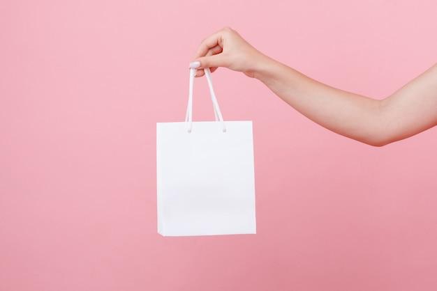 W ręku biała torebka pod logo na różowej przestrzeni
