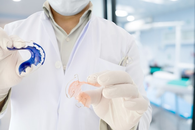 W ręku dentysta pokazuje aparat ortodontyczny ustalający