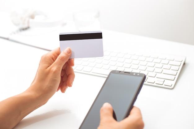 W ręku jest pusta biała karta kredytowa i telefon komórkowy do płatności internetowych.