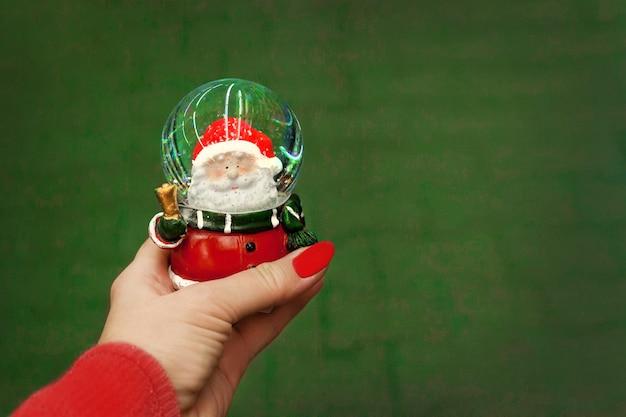 W ręku z czerwonym manicure'em świąteczna szklana czerwona kula z mikołajem