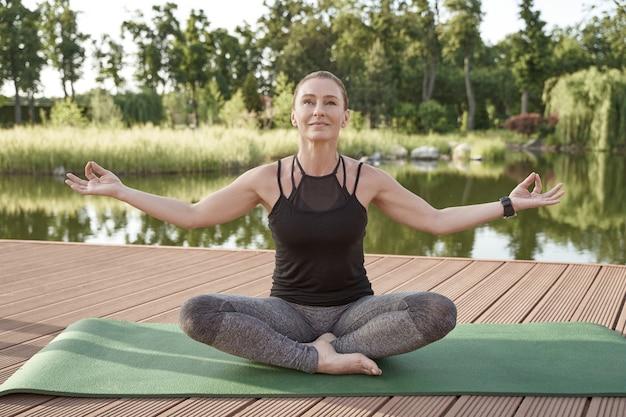 W równowadze piękna i szczęśliwa kobieta w sportowym stroju medytująca siedząca w pozycji lotosu na macie z