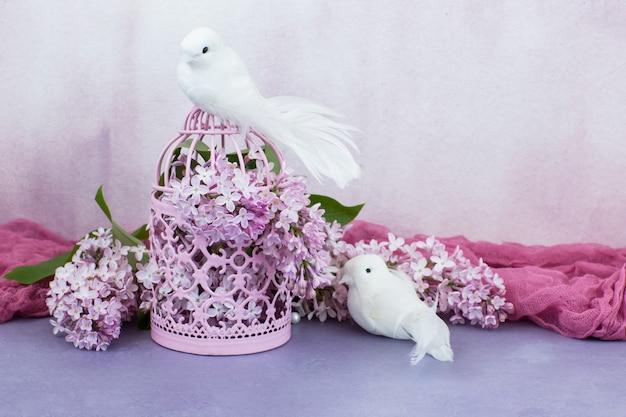 W różowej klatce różowy liliowy i dwa białe gołębie