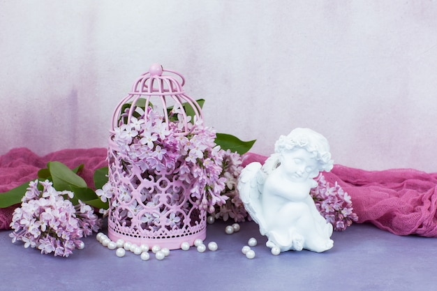 W różowej ozdobnej klatce różowy liliowy, perły i figurka anioła