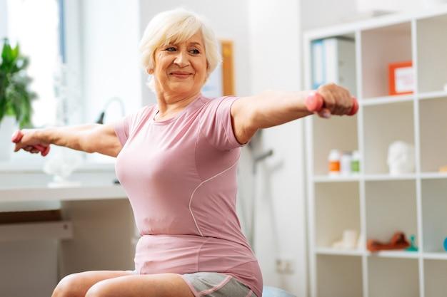 W sali do ćwiczeń. zachwycona starsza kobieta, ciesząca się swoim treningiem sportowym, będąc w sali do ćwiczeń