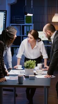 W sali spotkań korporacyjnych zróżnicowana, wieloetnowa grupa biznesmenów opiera się na stole konferencyjnym