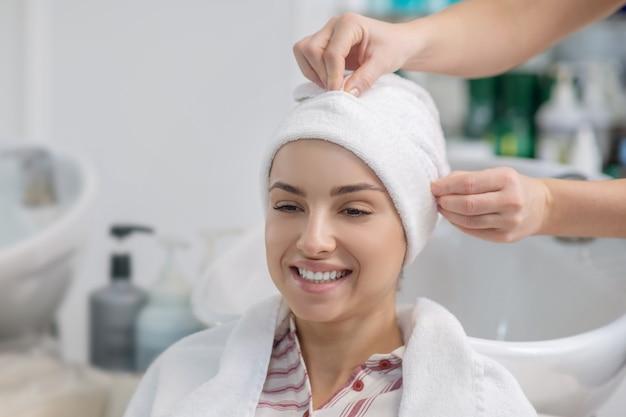 W salonie fryzjerskim. salon fryzjerski nakrywający włosy klientów ręcznikiem