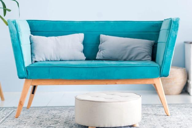 W salonie znajduje się nowoczesna niebieska sofa z poduszkami oraz puf. poziome zdjęcie