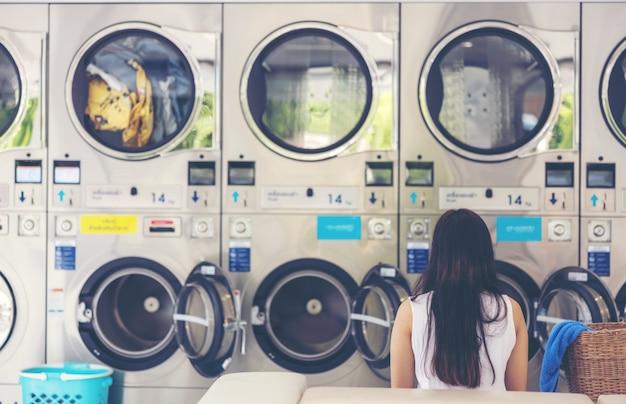 W samoobsługowej pralni z wieloma automatycznymi pralkami i zamglonym tłem, azjatka siedzi i używa swojego smartfona do pracy jako freelancer.