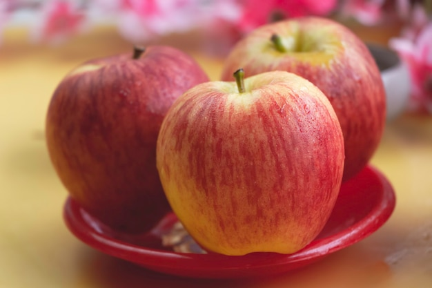 W selektywnym skupieniu jabłka z kroplami wody umieszczonymi w czerwonym naczyniu, rozmyte światło wokół
