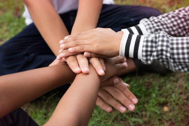 W selektywnym skupieniu się na ułożonych razem rękach małych dzieci, przyjaźni, współpracowniku, jedności, znaku sukcesu i mocy, rozmytym świetle wokół