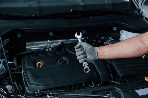 W sklepie. ręka mężczyzny w rękawicy trzyma klucz przed zepsutym samochodem