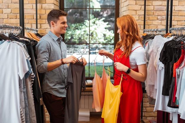 W sklepie z ubraniami. piękna młoda para uśmiechnięta i wyglądająca na zadowoloną, miło spędzając czas w sklepie z modną odzieżą