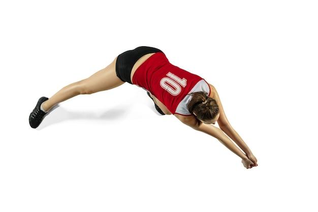 W skoku i locie. młoda siatkarka na białym tle na tle białego studia. kobieta w sportowej i tenisówki, trening, gra. pojęcie sportu, zdrowego stylu życia, ruchu i ruchu.