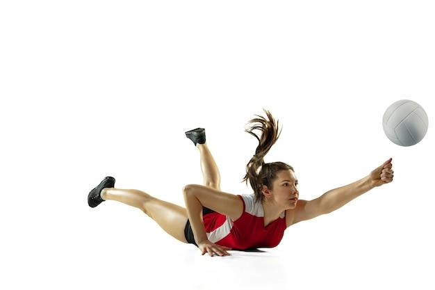 W skoku i locie. młoda siatkarka na białym tle na tle białego studia. kobieta w treningu sportowego i trampki, gra. pojęcie sportu, zdrowego stylu życia, ruchu i ruchu.