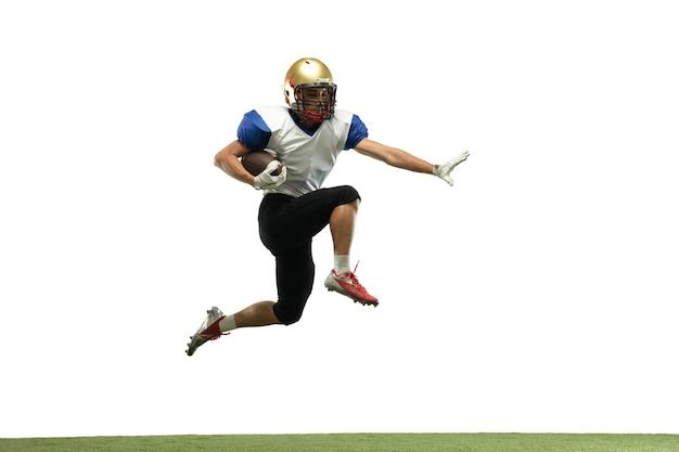 W skoku, locie. amerykański piłkarz na białym tle na tle białego studia z copyspace. profesjonalny sportowiec podczas gry w akcji i ruchu. pojęcie sportu, ruchu, osiągnięć.