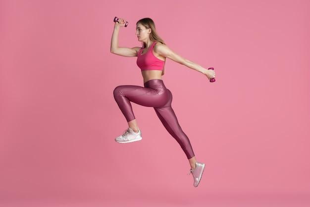 W skoku, locie. piękna młoda lekkoatletka ćwicząca w studio, monochromatyczny różowy portret