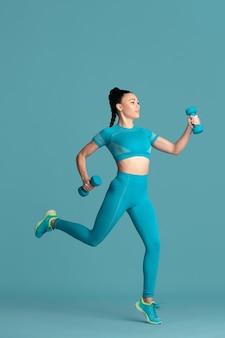 W skoku. piękna młoda lekkoatletka praktykujących, monochromatyczny niebieski portret. sportowy dopasowany model brunetka z ciężarkami. koncepcja budowy ciała, zdrowego stylu życia, piękna i działania.