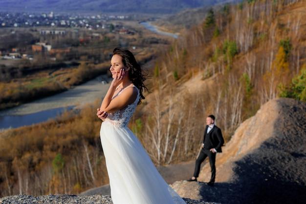 W słoneczny jesienny dzień na wzgórzu stoi panna młoda na pierwszym planie i niewyraźny pan młody w tle
