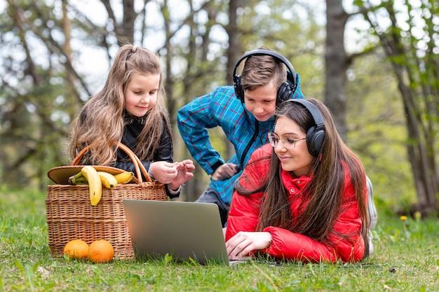 W słoneczny wiosenny dzień dwie siostry i brat odpoczywają na trawie obok kosza piknikowego w parku i oglądają film na laptopie