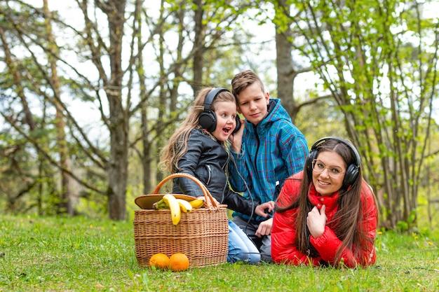 W słoneczny wiosenny dzień dwie siostry i brat w parku przy koszu piknikowym odpoczywają na trawie i słuchają muzyki