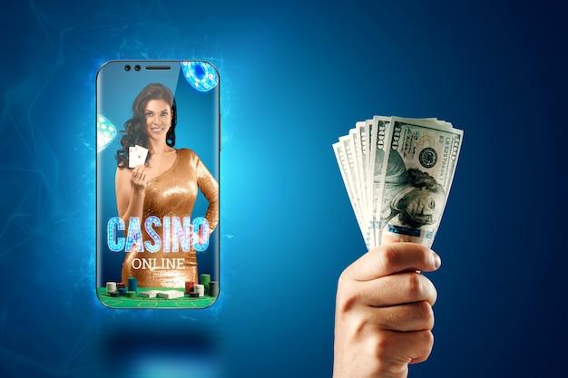 W smartfonie piękna dziewczyna z kartami do gry w dłoni i dłonią mężczyzny z wachlarzem dolarów. kasyno online, hazard, zakłady, ruletka. ulotka, plakat, szablon reklamy.