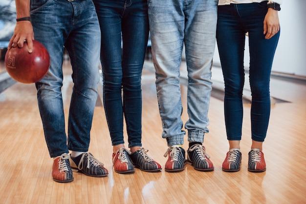 W specjalnych butach. przycięty widok ludzi w kręgielni gotowych do zabawy