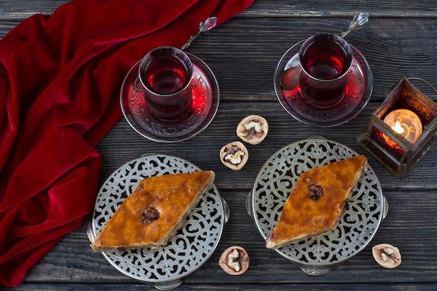 W srebrnych talerzach baklava, orzechy włoskie, latarnia i herbata. ramadan kareem.