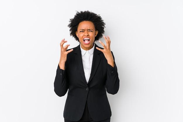 W średnim wieku african american biznes kobieta na białym tle krzyczy z wściekłości.