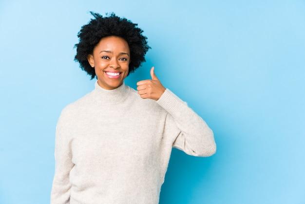 W średnim wieku african american kobieta na niebiesko na białym tle uśmiechnięty i podnoszący kciuk do góry