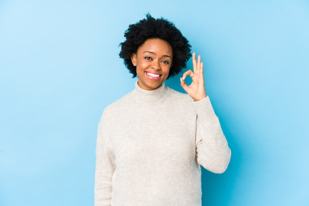 W średnim wieku african american kobieta na niebiesko na białym tle wesoły i pewny siebie, pokazując ok gest.