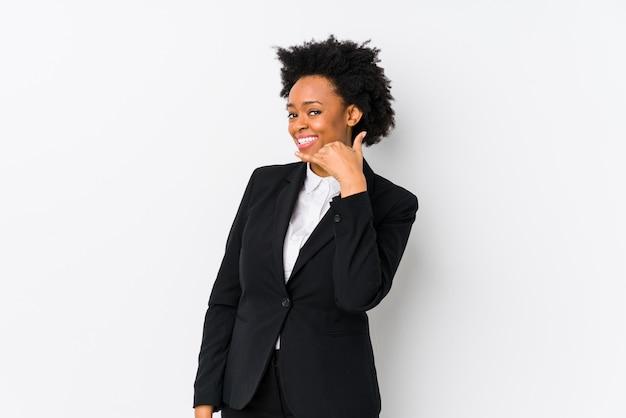 W średnim wieku amerykanin afrykańskiego pochodzenia biznesowa kobieta przeciw białej ścianie odizolowywającej pokazywać gesta rozmowy telefonicznej palcem
