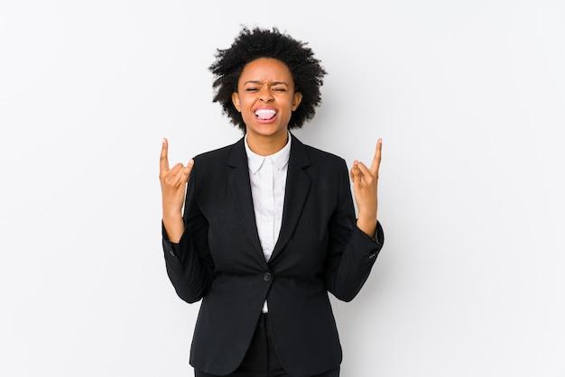 W średnim wieku amerykanin afrykańskiego pochodzenia biznesowa kobieta przeciw białej ścianie pokazuje rockowego gest z palcami