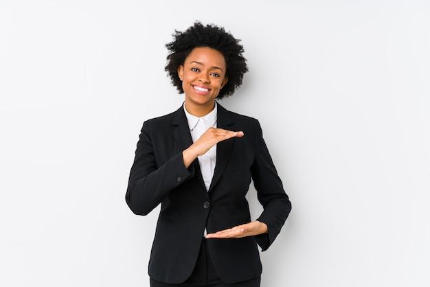 W średnim wieku amerykanin afrykańskiego pochodzenia biznesowa kobieta przeciw białej ściany mieniu coś obiema rękami