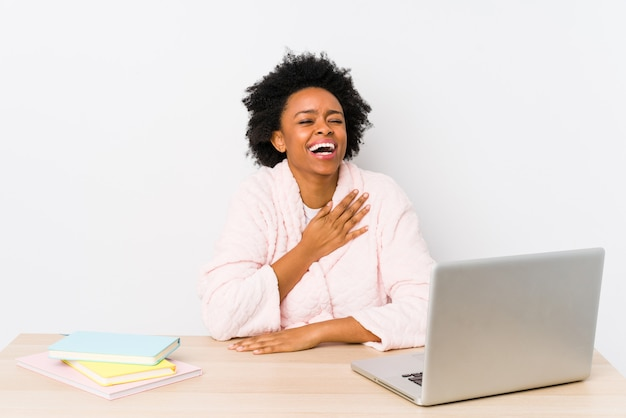 W średnim wieku amerykanin afrykańskiego pochodzenia kobieta pracująca w domu odizolowywa śmia się głośno trzymający rękę na klatce piersiowej.