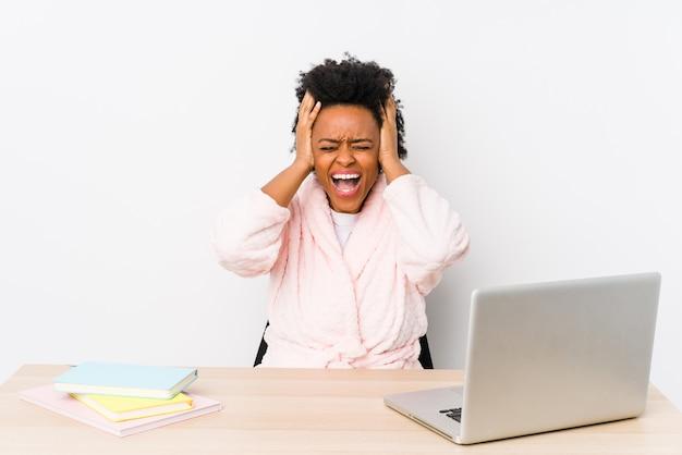 W średnim wieku amerykanin afrykańskiego pochodzenia kobieta pracuje w domu odizolowywał nakrywkowych ucho z rękami próbuje nie słuchać zbyt głośnego dźwięku.