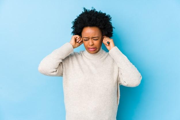 W średnim wieku amerykanin afrykańskiego pochodzenia kobieta przeciw błękitnej ścianie odizolowywał nakrywkowych ucho z rękami.