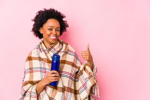 W średnim wieku amerykanin afrykańskiego pochodzenia kobieta uśmiecha się kciuk up i podnosi w campingu