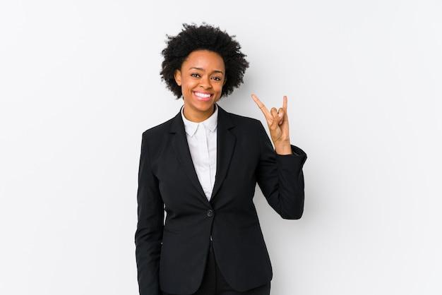 W średnim wieku amerykanina afrykańskiego pochodzenia biznesowa kobieta przeciw białemu tłu odizolowywającemu pokazywać rogu gest jako rewoluci pojęcie.